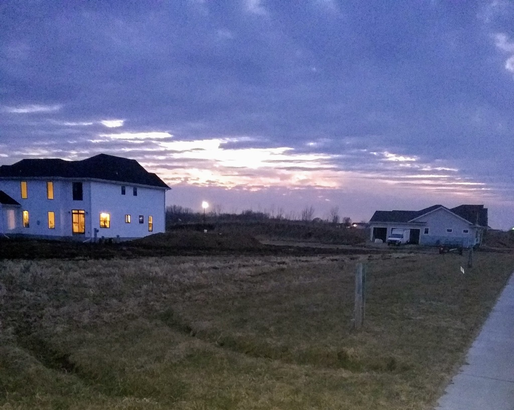 Recently built houses, one with windows brightly lit, the other dark with a truck parked in the driveway. The sun is setting behind a bank of purple clouds in the background between the two houses.